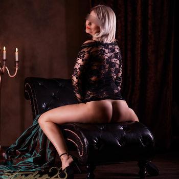 Dyana rücklings  sitzend im schwarzen Spitzenoberteil, zeigt ihren tollen Po
