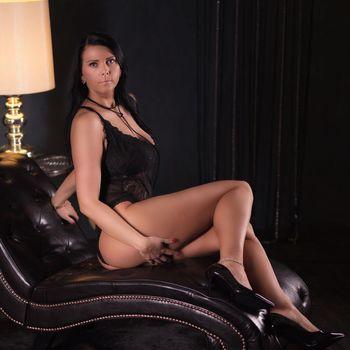 Natalie zeigt auf einer Liege sitzend ihren runden Po