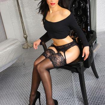 Die schwarzhaarige Mery stilvoll in schwarzen Dessous und sexy Strümpfen auf einem Stuhl posierend.