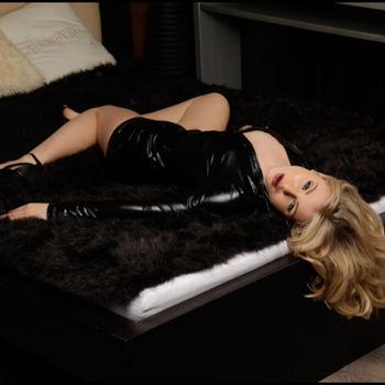Sophie Teen sich in High Heels und Lederjacke auf einem Fell rekelnd