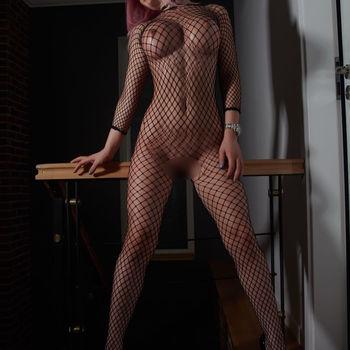 Katty zeigt ihren schlanken Körper, stehend, in einem sexy netz Outfit.
