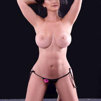 Das schöne Model Linda nur im String kniend, zeigt ihre wunderschönen, großen Brüste