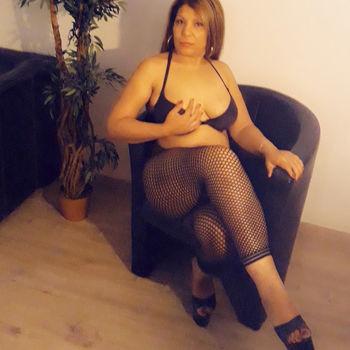 Melissa sitzt in schwarzer Wäsche mit übereinander geschlagenen Beinen und lässt dich so ihren sexy Körper sehen.