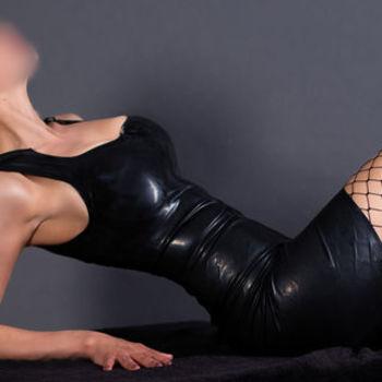Lena liegt in einem schwarzen Lederkleid und Netzstrümpfen auf dem Rücken und zeigt dir ihre schlanke Silhouette.