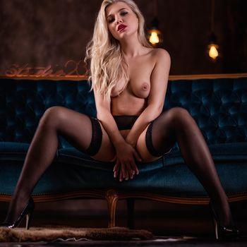 Sophie Teen nackt und breitbeinig auf einem Sofa sitzend mit den Händen zwischen den Beinen