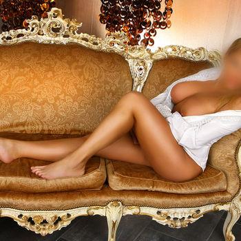 Katja auf einem Sofa liegend nur mit einem geöffneten Hemd welches die Brüste nicht bedeckt