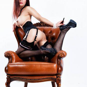 Nadja mit schönen Brüsten, kniend auf den Lehnen eines Sessels in reizender Wäsche und High Heels
