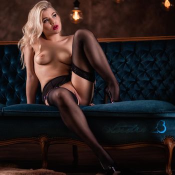 Sophie Teen nackt mit Strapsen und verträumtem Blick auf einem Sofa sitzend