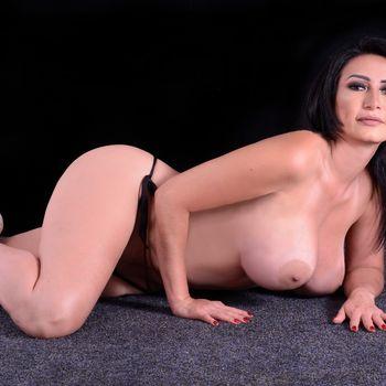 Linda sich ist nackt auf dem Boden rekelnd mit auffordernden Blick