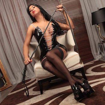 TS Pocohontas in einem sexy Lederoutfit, schwarzen Strümpfen und einer Peitsche in der Hand.
