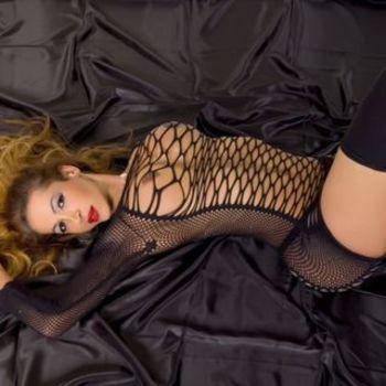 TS Agatha in schwarzem Netzoutfit liegend, sieht dich lasziv an.