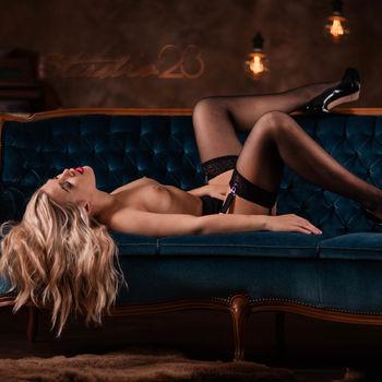 Sophie Teen in Strapsen und mit High Heels auf einem Sofa liegend