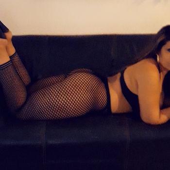 Melissa zeigt ihren kurvigen Körper auf einem Sofa liegend in schwarzen Netzstrumphosen.