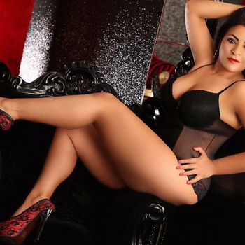 Angela sitzend in sexy Wäsche und High Heels, zeigt ihre langen Beine