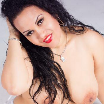 Natalia strahlt Dich aus hübschen äugen an. Ihr Busen ist nackt und ihre Lippen sind rot geschminkt.