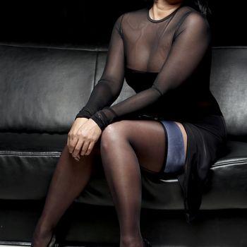die schwarzhaarige Esmeralda sitzend in eleganter Pose, schwarzem Kleid und Strümpfen wozu sie schwarze High Heels trägt