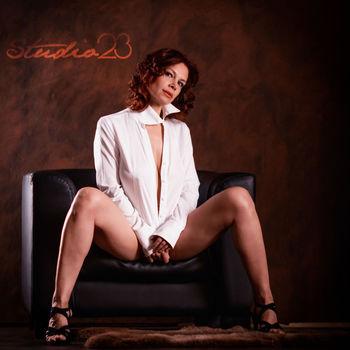 erfahrene Marta mit gespreizten Beinen und offenem Hemd im Lounge Sessel