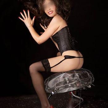 Asiatin Momoja rücklings sitzend in sexy Korsage und schwarzen Strümpfen.
