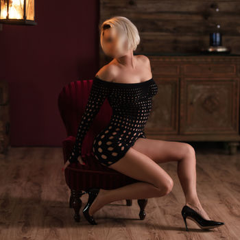 Die schöne Anna auf einem Sessel seitlich sitzend im kleinen, schwarzen Netzkleid, werden ihre endlos langen Beine betont