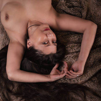 Moni liegend im Porträt mit nackten Brüsten und verführerischem Lächeln