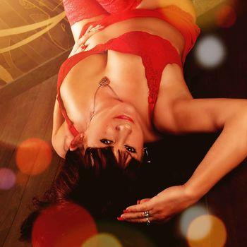 Sabrina Bizarre in roter Wäsche verträumt auf dem Rücken liegend.