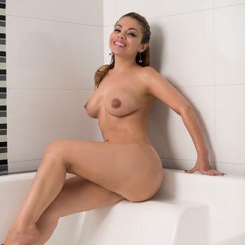 Lorena sitzt nackt auf einem Badewannenrand und zeigt ihren sexy Körper.
