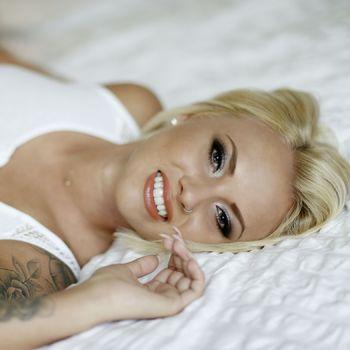 Junge Blondine Nele liegend mit einem hinreissendem Lachen