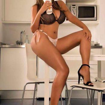Die schlanke Alina sitzt in sexy Dessous auf einem Tisch.