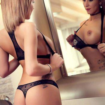 Julia in schwarzer Wäsche vor einem Spiegel stehend, mit Blick auf ihre rechte Brust.