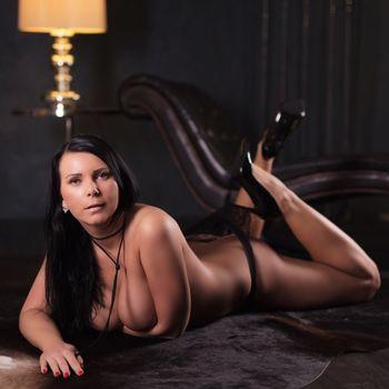 Natalie auf dem Bauch liegend mit dem Hacken ihren High Heels den Slip anhebend