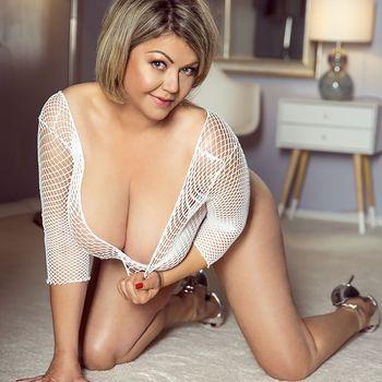 Die schöne Natali in weißem Netzoberteil und silbernen High Heels kniend.