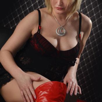 Blondine Patrizia im schwarzen Body und roten Lack Overknees