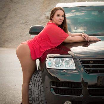 Sarah in rotem Oberteil posiert lasziv an einem Auto.