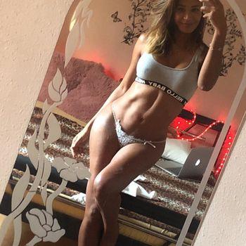 Die brünette Kalissa posiert vor einem Spiegel in sportlicher Wäsche.