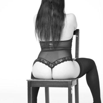 Laura sitzt rücklings in schwarzer Wäsche und sexy Strümpfen auf einem Stuhl.