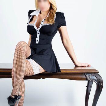 Franzi Schmidt im sexy Zimmermädchenkleid und Netzstrümpfen, auf einem Tisch sitzend
