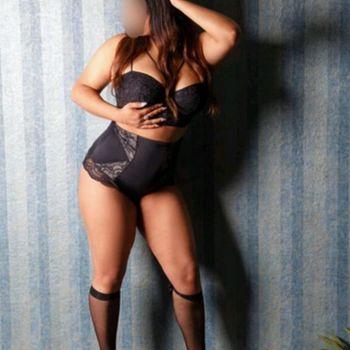Yessika zeigt ihre geilen Kurven stehend in schwarzer Unterwäsche.