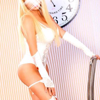 Langhaarige Blondine Anja ins sexy weißem Body an einen Stuhl gelehnt