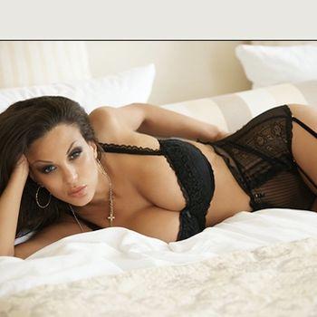 Sarah liegt einladend auf dem Bett und trägt aufreizende schwarze Wäsche.