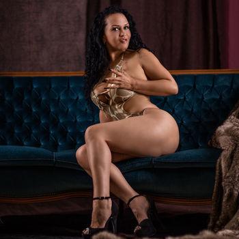 Natalia sitzt im goldenen Tangkini auf einer Petrolfarbenen Chesterfield Couch